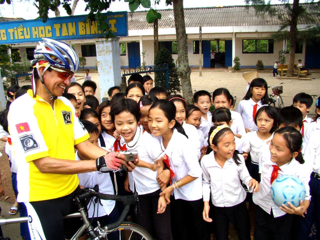 Bicyclist stops at local school in Vietnam