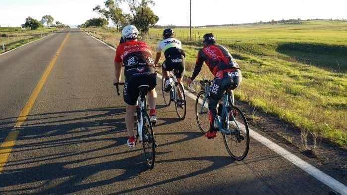 Cyclists riding past green fields outside of Ensenada, California